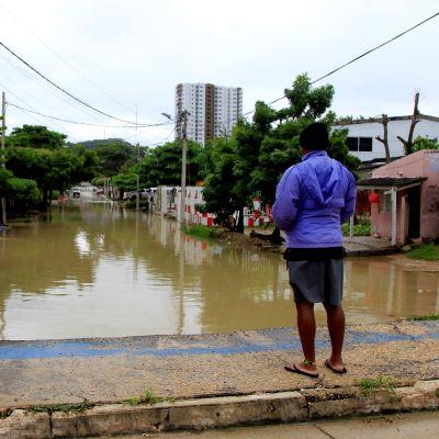 Kaksi kolumbialaista miestä katselee hirmumyrsky Iotan aiheuttamia tulvavahinkoja turistikaupunki Cartagenan lähiössä.