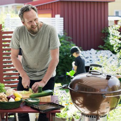 Anders Samuelsson utomhus i solen framför ett bord med fräsha grönsaker och rotsaker.
