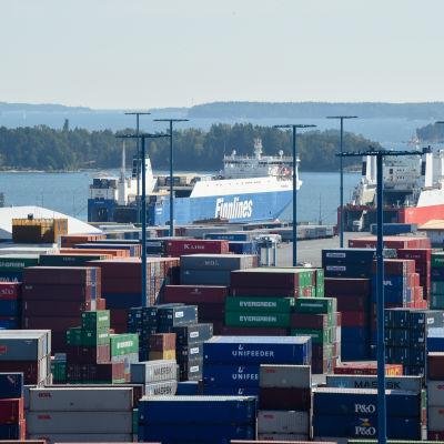 Vy över Nordsjö hamn med containrar i förgrunden och skärgård och fraktfartyg i bakgrunden.