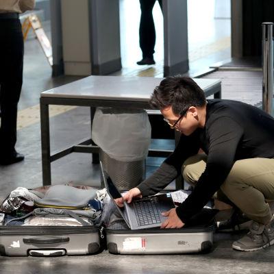 Passagerare på Atatürkflygplatsen i Istanbul placerar sin laptop i den incheckade bagaget.