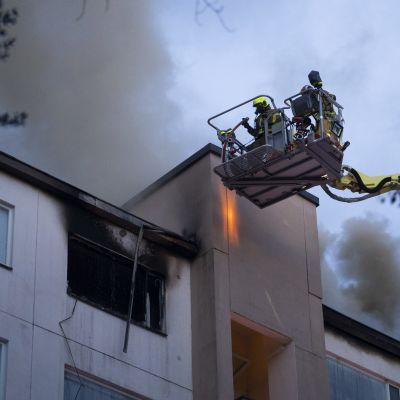 Två brandmän i lyftkran släcker en eldsvåda i ett höghus i Lahtis.