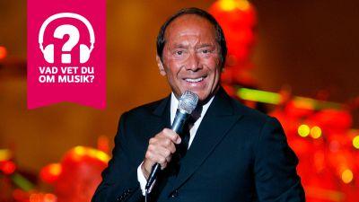 Paul Anka ler och sjunger i en mikrofon som han håller i handen.