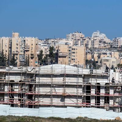 Kerrostaloa rakennetaan etualalla. Taustalla näkyy kaupunkimaisemaa.