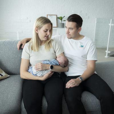 Anniina ja Joonatan Liedes lapsensa kanssa sohvalla.