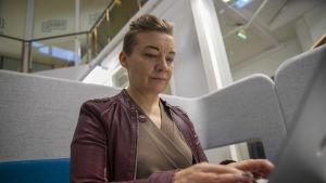 Katleena Kortesuo istuu ja näpyttää tietokonetta.