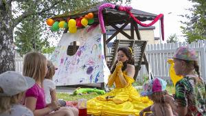 Ammattiprinsessa istuu lasten ympärillä syntymäpäiväjuhlilla.