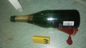 En flaska för mousserande vin ligger i en blodpöl. Bredvid dem är en gul brottsutredningslapp med siffran tre.