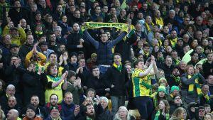 En supporter håller upp en halsduk då Norwich City spelar.