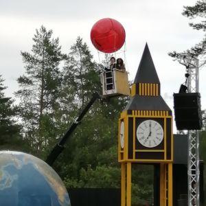 En röd ballong som lfter till väders med folk i korgen, pjäsen Jorden runt på 80 dagar på Raseborgs sommarteater.
