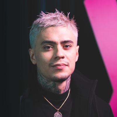 Rap-artisti Mikael Gabriel katsoo kameraan pinkkimustaa taustaa vasten.