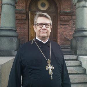 Markku Salminen, kyrkoherde vid Helsingfors ortodoxa församling, står framför en trappa in till Uspenskijkatedralen på Skatudden i Helsingfors. Han ser allvarsam ut och blickar ut bakom kameran.