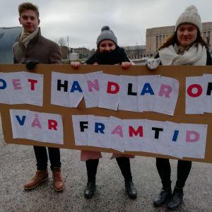 """Tre unga demonstranter med ett plakat med texten """"Det handlar om vår framtid""""."""