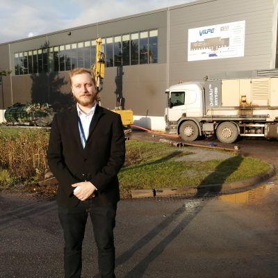 Vilpe Oy:n toimitusjohtaja seisoo tehtaan edustalla, jossa parhaillaan porataan maalämpöjärjestelmää tehtaan pihalle.