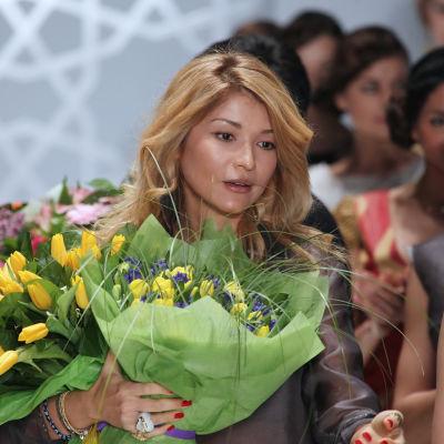 Gulnara Karimova med en stor blombukett i handen.