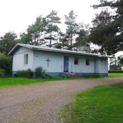 Ett blått hus med kors på väggen som är Ingå församlings ungdomshus.