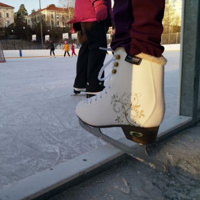 Luistelija astumassa Tampereen Koulukadun tekojääkentälle