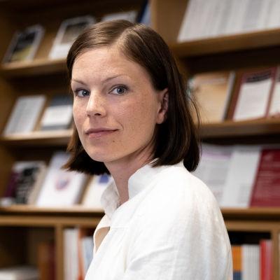 Sanna Kurronen katsoo taakseen, taustalla näkyy EVAn julkaisuja kirjahyllyssä.