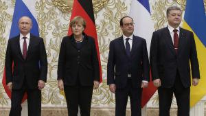 Tre herrar och en dam förhandlar om en lösning på Ukrainakrisen.