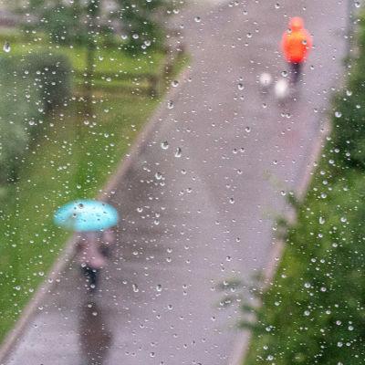 Ihmisiä kävelee sateessa.