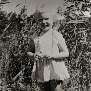 Tutkija Taina Kinnunen pikkutyttönä mustavalkoisessa valokuvassa kesäisessä maisemassa.
