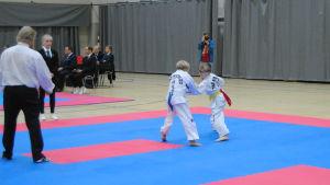 Två unga idrottare går en match i taekwondo.
