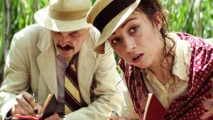 Mies tekee muistiinpanoja, nainen katsoo vieressä. Ovat jonkinlaisessa korkeassa ruohikossa tmv.