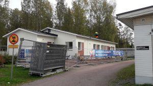 Vita byggnader med tillfälliga stängsel rumtomkring. En skylt som visar att det är förbjudet att klöra in på området. Grusväg mellan byggnaderna och träd i bakgrunden.