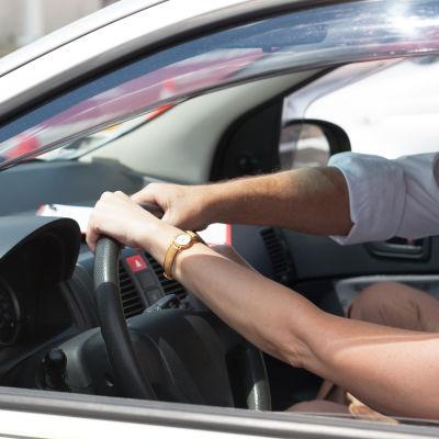 Förarens och bilskollärarens händer möts på ratten.