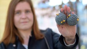 En kvinna håller i två virkade bollar som ser ut som getingbon.