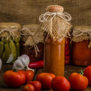 Hemgjord tomatsås i glasburk. I bakgrunden andra inlagda grönsaker och färska tomater och vitlök.