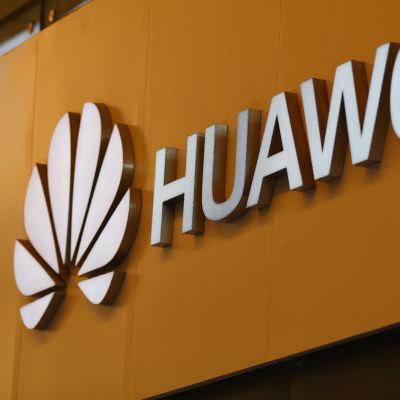Huaweis logotyp mot orange bakgrund.