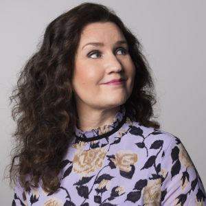 Pia-Maria Lehtola violetinvärisessä kukkakuosisessa paidassa.