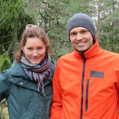 En kvinna i rödbrunt hår  och grön anorakliknande ytterrock och  en man i grå mössa och orangefärgad jacka står i en granskog. De ser glada ut.