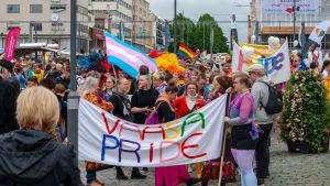 Ett pridetåg med folk, banderoller och regnbågsflaggor.