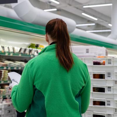 Lappeenrannan Prisman käytävällä työntekijä katsoo paperia jouluruoka-laatikoiden vieressä.