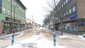 En folktom gågata. Till vänster och höger syns byggnader med olika affärer.
