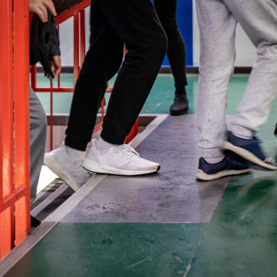 anonyymejä jalkoja koulun käytävällä