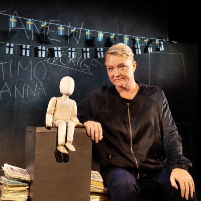 Anna Takanen istuu Lilla Teaternin näyttämöllä harjoitustauolla. Takanaan liitutaulu, jossa roikkuu Suomen ja Ruotsin lippuja. Hän esittää monologia, joka pohjautuu omiin kokemuksiin sotalapsen lapsena.