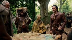 Devon Terrell spelar Arthur i tv-serien Cursed. På bilden syns ett skogslandskap där Terrell står längst till höger tillsammans med några andra fantasikaraktärer runt ett bord där en karta ligger utbredd.