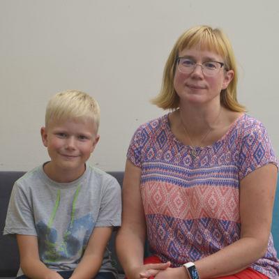 En mamma med sin son sitter på en blå soffa i ett eftis. De tittar in i kameran och ler.