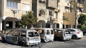 En rad utbrända bilar står framför en byggnad.