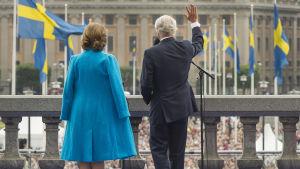 Drottning Silvia och Kung Carl XVI Gustaf med ryggen till står och vinkar ut mot folkmassor.