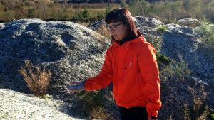 Stormossens informationschef Nina Lindman håller i krossat glas. Hon står brevid högar av krossat glas som ska bli jordfyllnad och grund för ett område för kompostjord vid Stormossen.