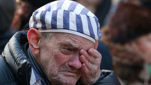 En man sörjer under en ceremoni i Auschwitz som ordnades 75 år efter att lägret befriades.