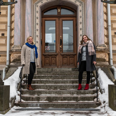 Två kvinnor står på en trappa