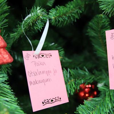 Kuvassa Hope ry:n toivepuu, jossa on roikkuu lasten lahjatoiveita