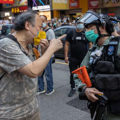 Mielenosoittaja osoittaa sormella poliisia, molemmilla kasvomaskit.