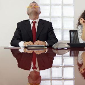 Kaksi tylsistynyttä kollegaa leikkivät kynällä.