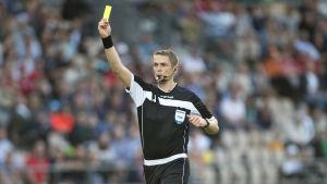 Mattias Gestranius håller upp ett gult kort.
