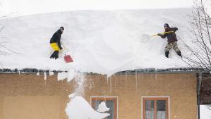 Två män skottar snö från ett tak i Filzmoos i Österrike. Flera byggnader i landet har kollapsat av snömassorna.